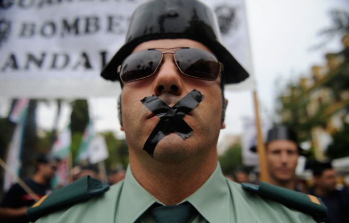 A Spanish civil guard with his mouth sealed with tape attends a demonstration of public service workers against government's spending cuts in Sevilla.