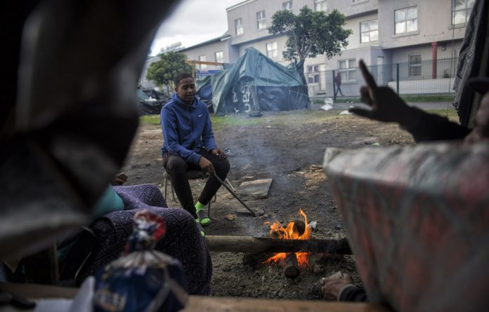 Muzaniel Abrahams and his family camp outside Steenvilla social housing apartments after being evicted from the complex about a month ago.