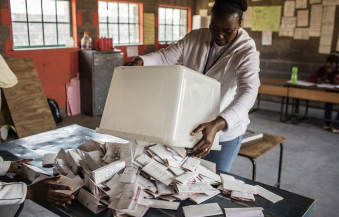 A Lesotho Independent Electoral Commission marshal starts the counting process at the end of voting in the Lesotho parliamentary elections in Maseru.