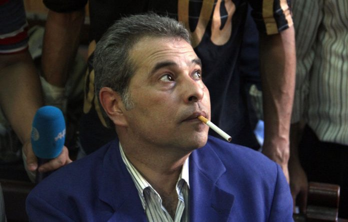 Egyptian talk show host Tawfiq Okasha attends his trial on charge of calling for the murder of President Mohamed Morsi