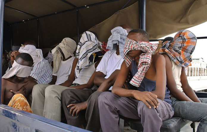 Suspected al-Shabab fighters sit on a tuck after being rounded up by Somalia's troops during an operation at Elasha Biyaha.