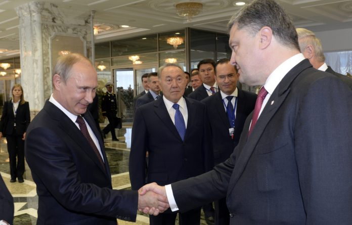 Russian President Vladimir Putin shakes hands with his Ukrainian counterpart Petro Poroshenko