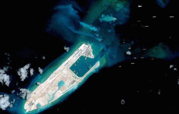 Troubled waters: A satellite image of what is claimed to be an airstrip under construction on Fiery Cross Reef in the Spratly islands in the South China Sea.