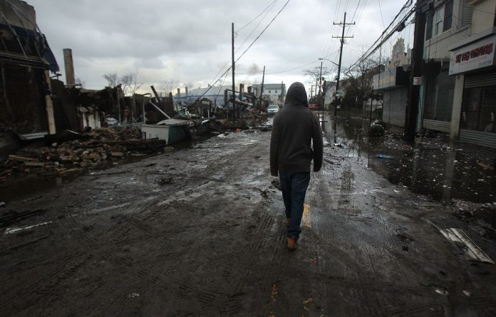 A man walks by homes and businesses destroyed during Hurricane Sandy in New York City.