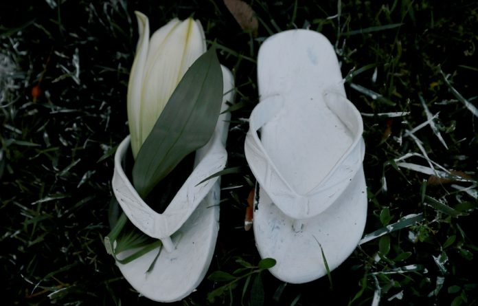 A pair of flip-flops with a flower sit among the other pairs of painted white shoes