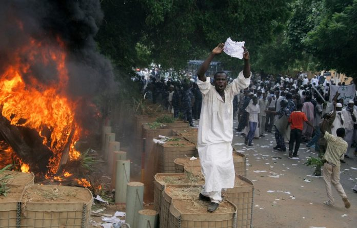 A Sudanese demonstrator shouts slogans as policemen try to disperse protesters after they torched the German embassy in Khartoum during a demonstration against a low-budget film mocking Islam.