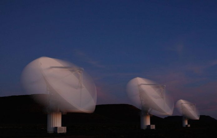 Radio telescope dishes of the KAT-7 Array shift their alignment in a long exposure picture taken at the proposed South African site for the Square Kilometre Array