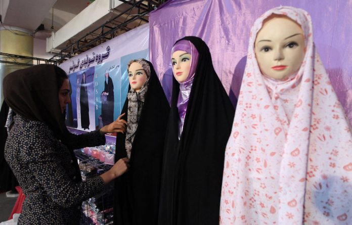 Female booth attendants at a global trade fair and shops selling men's ties have become targets in a strict crackdown by Tehran police.