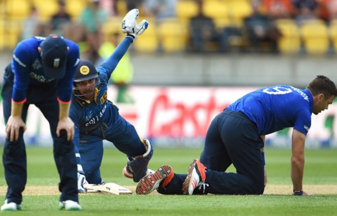 Sri Lanka batsman Kumar Sangakkara survives a run out chance as England players Eoin Morgan and James Anderson
