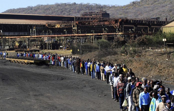 Zimbabwe Iron and Steel Company workers walk to its plant in Redcliff