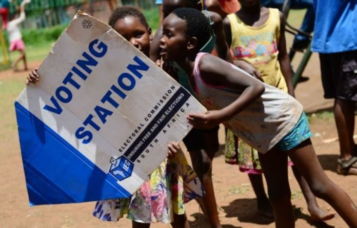 Children play with IEC boards in Soweto.