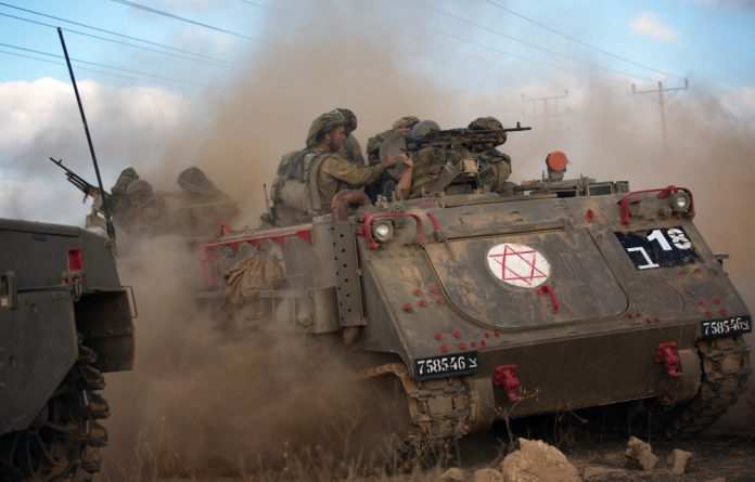 A convoy of Israeli armoured personnel carriers move towards the Israeli-Gaza border.