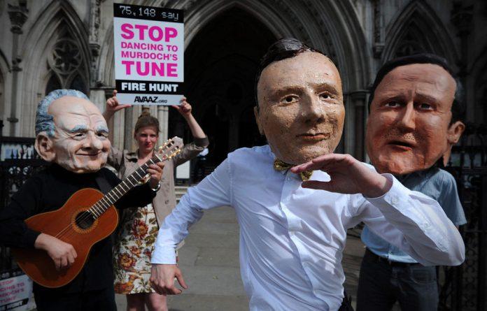 Demonstrators wear masks depicting British Prime Minister David Cameron