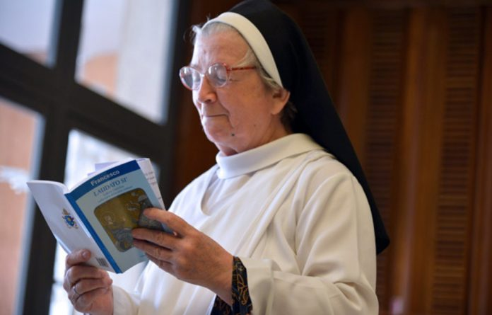 A nun reads Pope Francis's encyclical Laudato Si during its official presentation on Thursday at the Sinod hall at the Vatican.