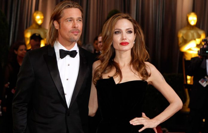 Actor Brad Pitt poses with his partner actress Angelina Jolie on the red carpet at the 84th Academy Awards in Hollywood.