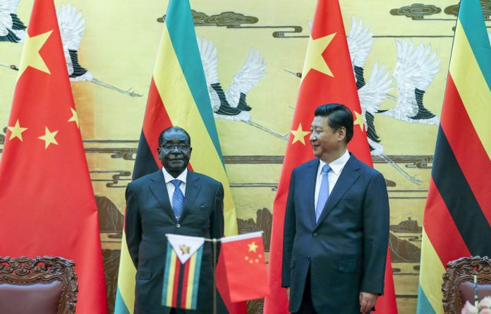 Zimbabwean President Robert Mugabe and Chinese President Xi Jinping pose at a signing ceremony in Beijing.