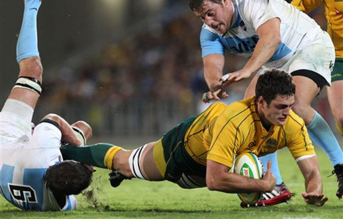 Australia's Dave Dennis is tackled by Argentina's Julio Farias Cabello