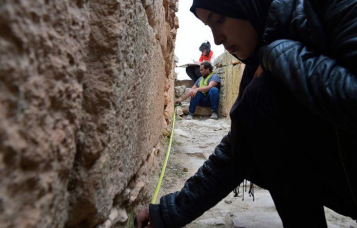 Experts and students from Algiers Universitys Archaeology Institute work on one of the Jeddars pyramid tombs