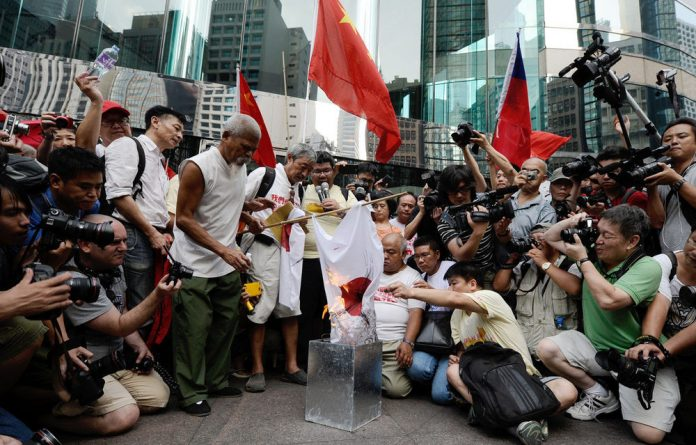 Activists burn Japanese flags during a demonstration over a group of disputed islands outside the Japanese consulate in Hong Kong.