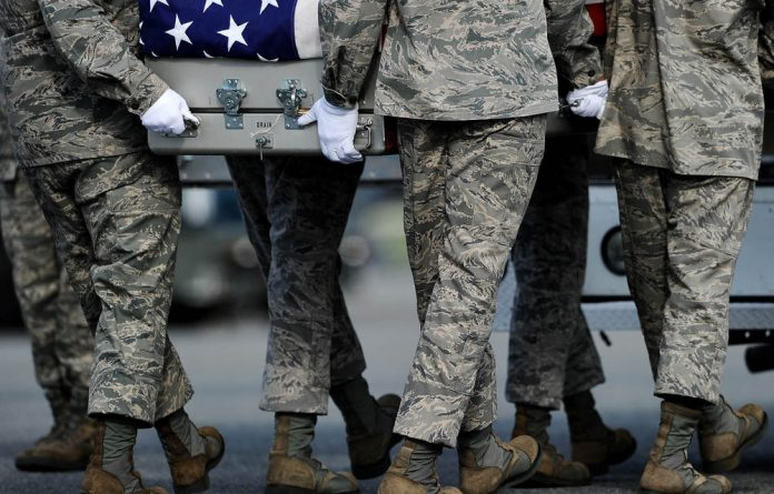 US Air Force soldiers carry the flag-draped transfer case containing the remains of Air Force Maj. Walter D. Gray