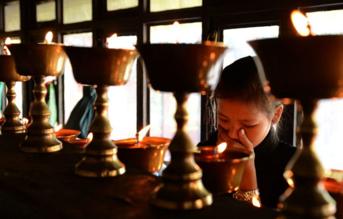 Daughter of Mount Everest avalanche victim Ang Kazi Sherpa lights oil lamps at Sherpa Monastery in Kathmandu on April 20 2014.
