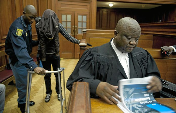 Xolile Mngeni is assisted in court by a policeman while his lawyer