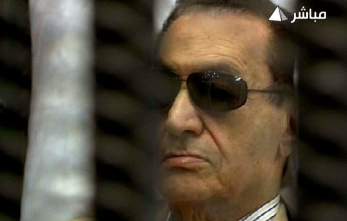 An image grab taken from Egyptian state TV shows ousted Egyptian president Hosni Mubarak sitting inside a cage in a courtroom during his verdict hearing in Cairo.