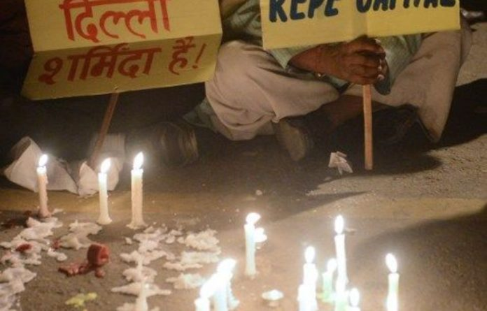 Indian protestors look at candles and placards during a rally in New Delhi on