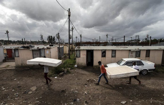 Put to bed: Men move their possessions back after evictions last Friday at the Barcelona 2 transit camp in Lamontville. Abahlali baseMjondolo was able to halt the 'unlawful' evictions.