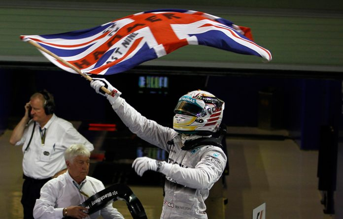 Lewis Hamilton waves the Union flag with the words 'Hammer time' in celebration after winning the world championship at Abu Dhabi on November 23 2014.