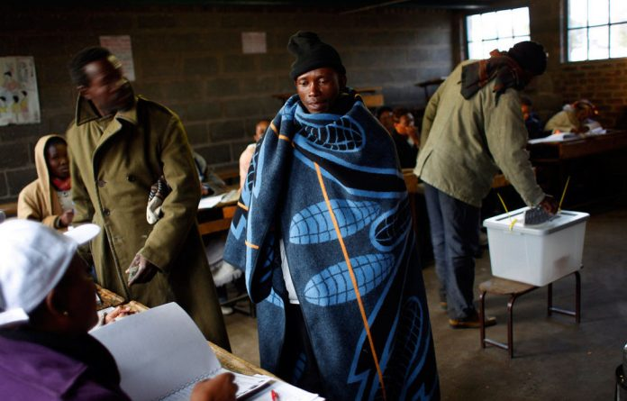 A Lesotho man prepares to vote in Maseru on Saturday. Lesotho's ruling party seems to have taken the lead