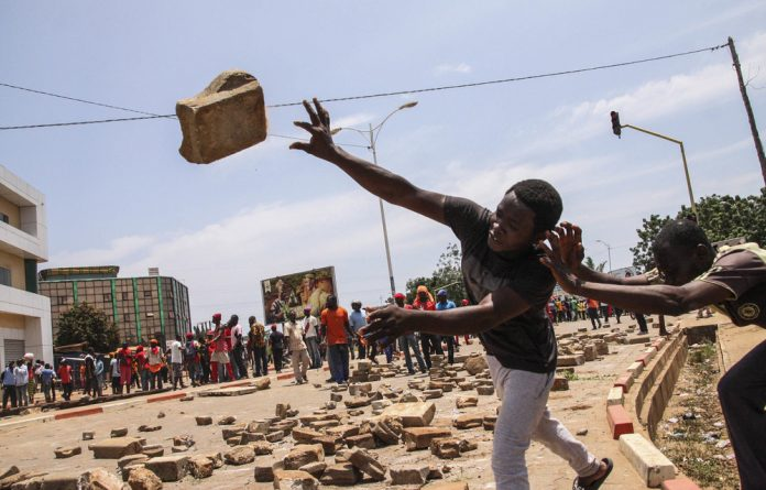 Protesters hurl bricks at Togolese security forces during a demonstration against President Faure Gnassingbé in Lomé.