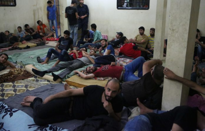Palestinian migrants in a police building in Rafah. Egyptian naval forces arrested the would-be immigrants and sent them back to Gaza