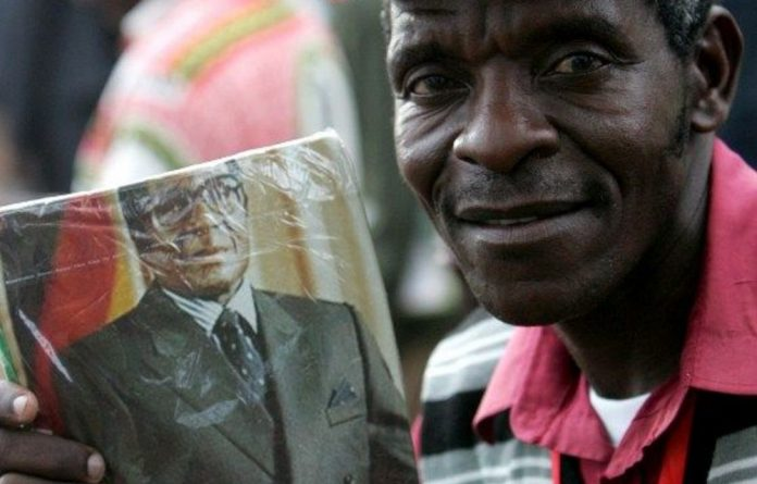 A man holds a picture of Zimbabwe's President and leader of ruling Zanu-PF party Robert Mugabe.