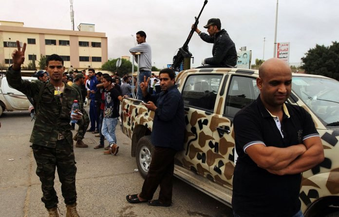 Libyan army soldiers outside Benghazi's al-Jala hospital as wounded victims from clashes are rushed in to be treated.