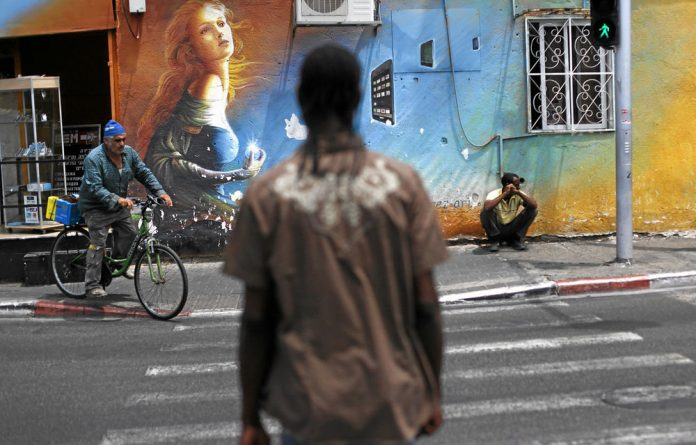 Unwelcome: African migrant workers on a street corner in Tel Aviv.