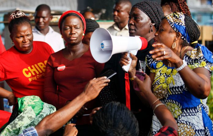 Women attend a protest on Wednesday to mark 100 days since nearly 300 schoolgirls were abducted. A day before the protest