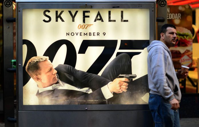 A man stands in front of a poster advertising the latest James Bond movie Skyfall in New York.