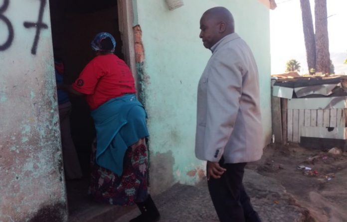 Ida Plaatjies takes Land Reform deputy minister Mcebisi Skwatsha into one of the homes on the Marlenique Estate in Simondium.