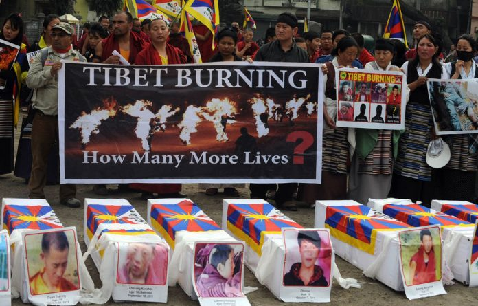 Tibetans offer prayers near mock coffins to represent the victims of self-immolation during a rally in China.