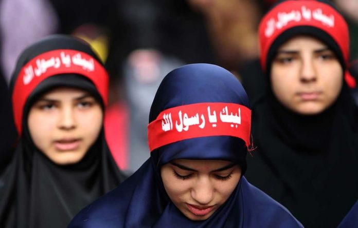 Women wear headbands reading 'at your service God's prophet' at a rally denouncing the film 'Innocence of Muslims'.
