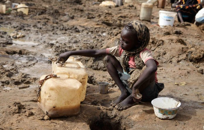 A young girl fetches murky water from a hole dug near a dried well in Jamam