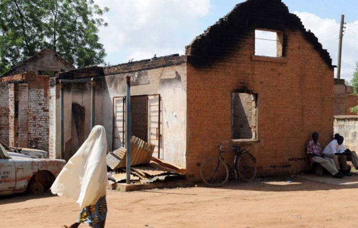 File picture from 2009 showing a veiled woman walking near a burnt police station in the northern Nigerian city of Potiskum