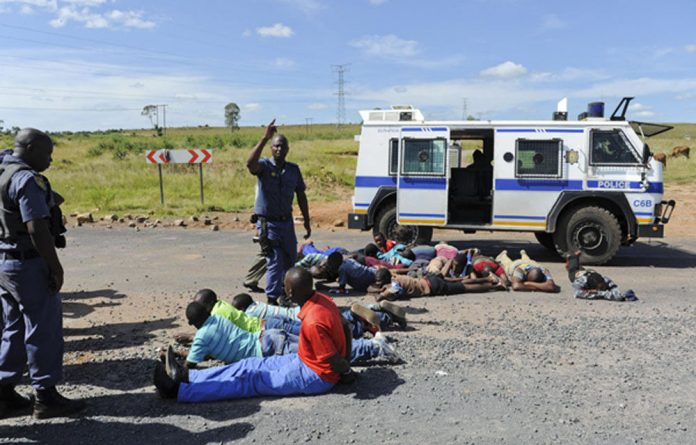 Police officers arrest protesters from Zithobeni for barricading roads with tyres and escalating tension.