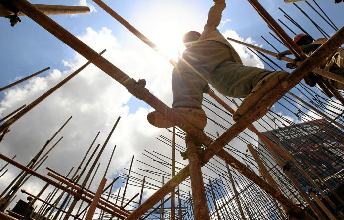 A construction worker walks on scaffolding along the Nairobi-Thika highway project in Nairobi.