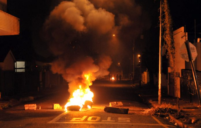 Rioters retreat down a side street after setting fire to tyres near Jules Street in Jeppestown during running battles with the police through out the night on April 17.