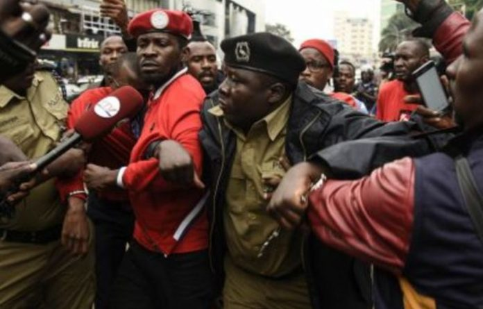 Poor man's hero: Musician-turned-politician Robert Kyagulanyi is arrested by police during a demonstration in July in Kampala against a new tax on social media use.