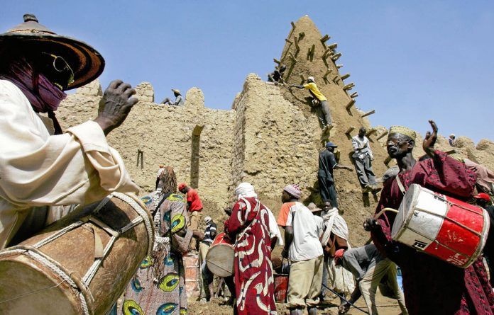 Workers restore Timbuktu's Great Mosque in 2006.