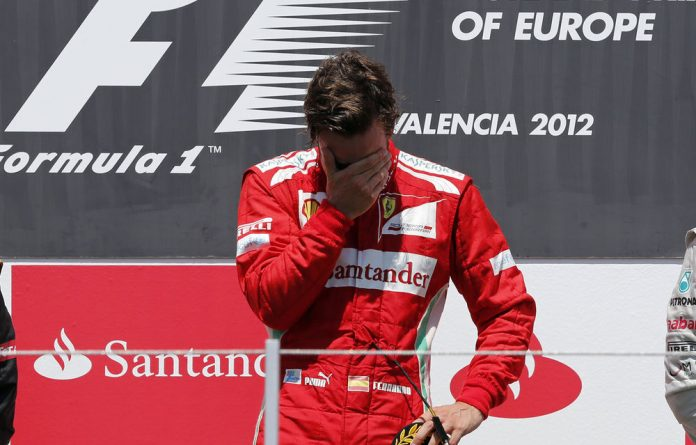 Ferrari Formula One driver Fernando Alonso of Spain reacts on the podium after winning the European F1 Grand Prix at the Valencia street circuit June 24