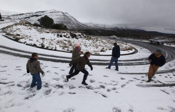 Families brave the cold to play in the snow outside Fraserburg in the Northern Cape.